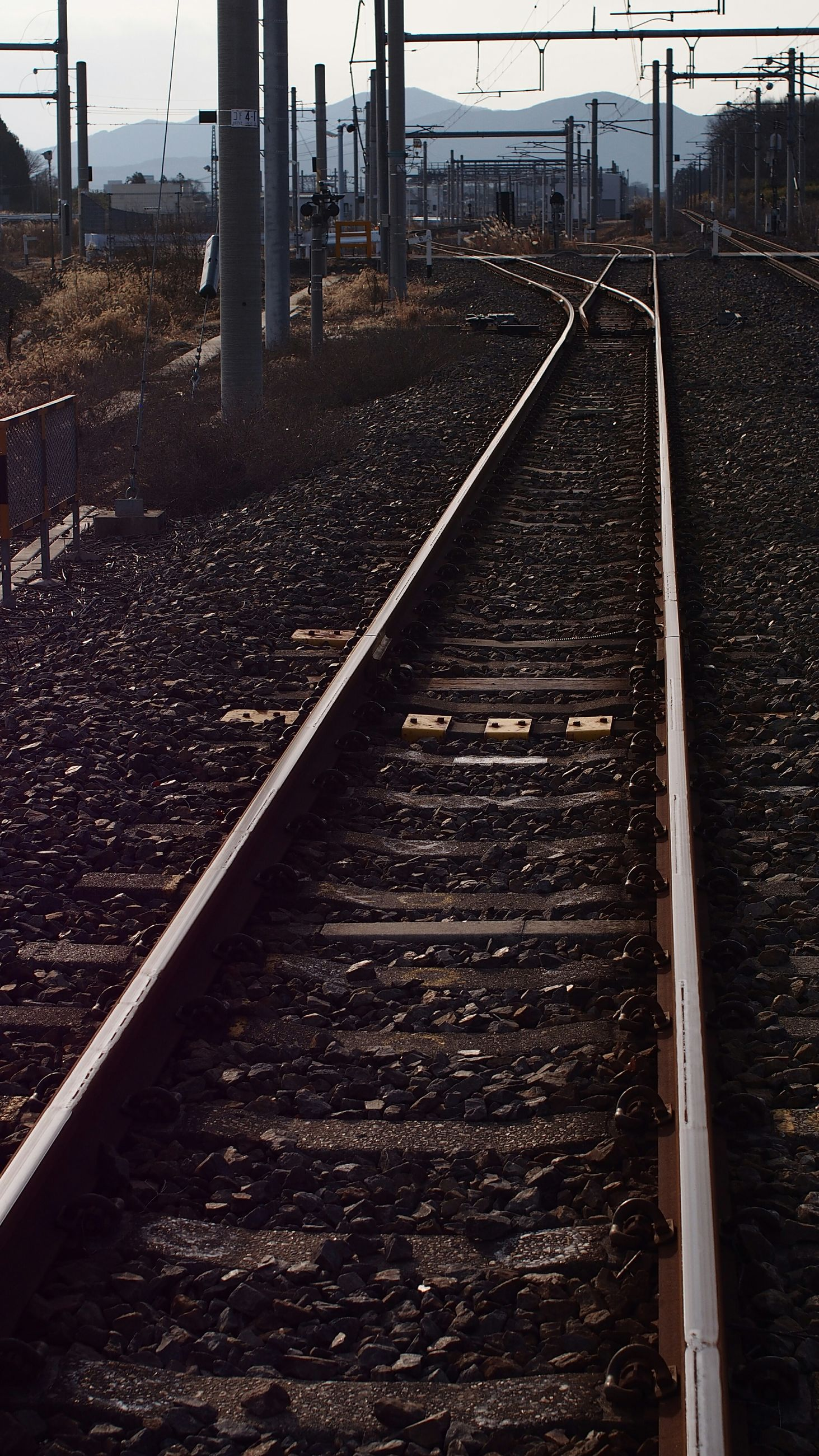 railroad track, the way forward, rail transportation, diminishing perspective, vanishing point, transportation, built structure, architecture, railway track, surface level, public transportation, straight, long, metal, sky, connection, day, railroad station platform, building exterior, no people
