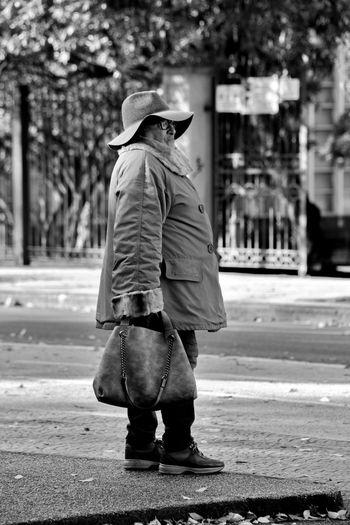 Side view of man wearing warm clothing standing on sidewalk