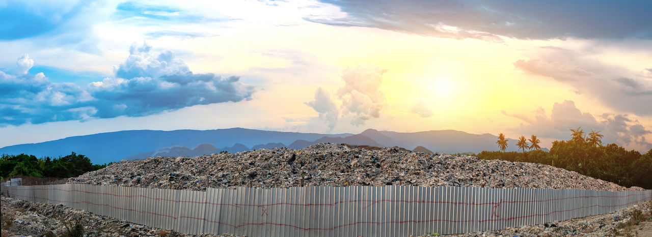 Mountain large garbage pile and pollution surrounded by iron fences at the sun is setting