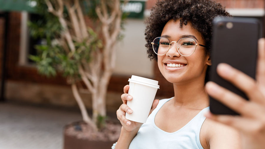 Portrait Of Teenage Girl Taking Selfie On Mobile Phone While Holding Disposable Cup