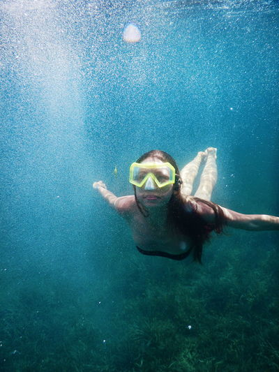 Young Woman Swimming In Undersea