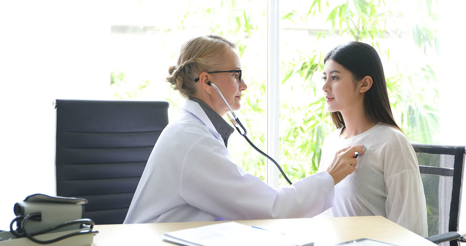 Doctor Checking Patient On Table At Clinic
