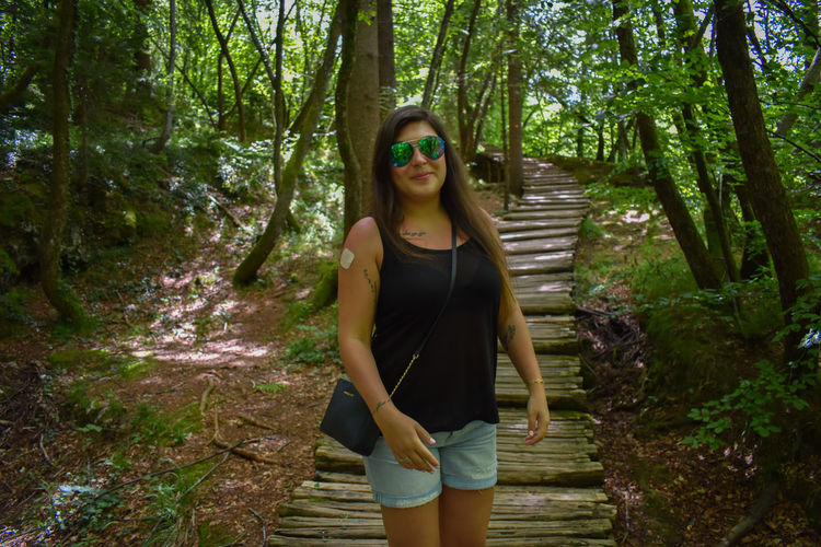 Plitvice Lake National Park Plitvice Lakes National Park Plitvicka Jezera Nacionalni Park Beautiful Woman Casual Clothing Fashion Forest Front View Glasses Hairstyle Land Leisure Activity Lifestyles Looking At Camera One Person Outdoors Plant Plitvice Plitvice Lakes Plitvice National Park Plitvicelakes Plitvickajezera Portrait Real People Smiling Standing Sunglasses Three Quarter Length Tree WoodLand Young Adult Young Women