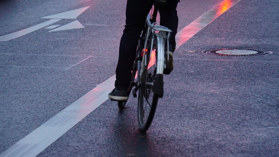 Low Section Of Man Riding Bicycle On Street During Sunset