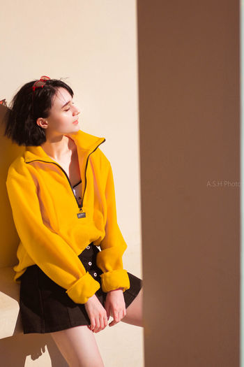 Side view of young woman standing against yellow wall