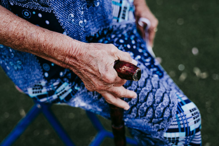 Close-up of senior woman holding walking cane