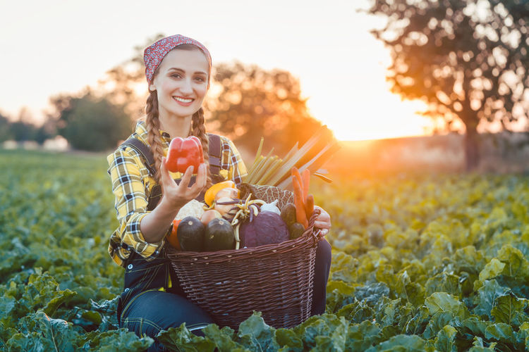Smiling Woman Holding Vegetables In Basket While Sitting On Field During Sunset