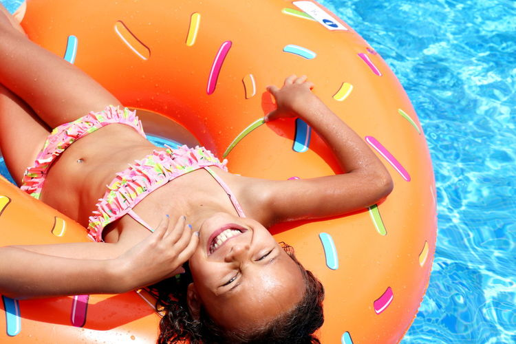Portrait of smiling woman lying in swimming pool