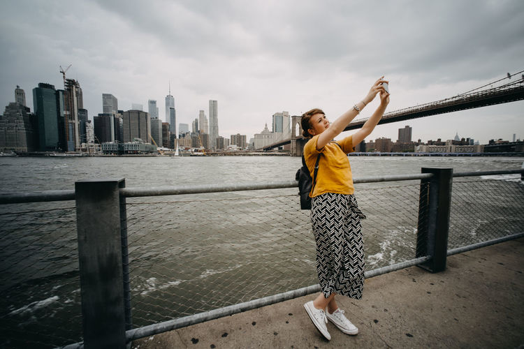Woman taking selfie while standing against river in city