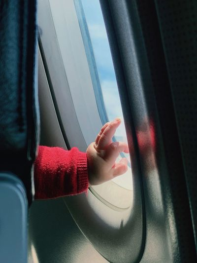 Close-up of baby hand by airplane window