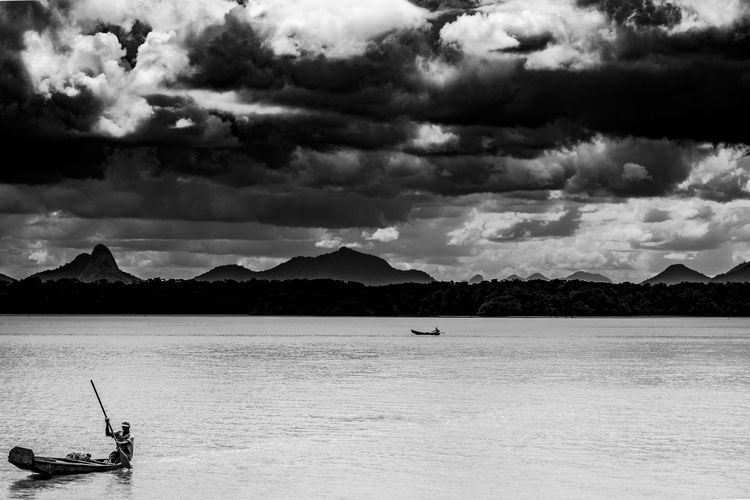 Ilha das caieras IlhadasCaieiras Black Blackandwhite Blackandwhitephotography Boat Clouds Contrast Fishing Boat Isle Mountain People River Sea White EyeEmNewHere