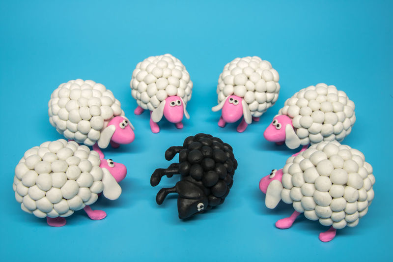 Concept - A group of white polymer clay sheep surrounding a black sheep lying on its side An idea of reaching out to someone's different. Not turning your back to a hurting individual that is different. Black sheep symbolizes a negative or an odd person, and the white sheep flock represents friends or society, gathering around as if to check what's wrong. Can also be interpreted as a beat down or a social punishment, or criticizing. Accused Black Blamed CrucifyMe Cute Danger Different Family Friendless Frightened  Help Innocence Isolated Judging Offended Outcast Punishment Raped Reach Out Rehabilitation Society SUPPORT Trauma Victim White