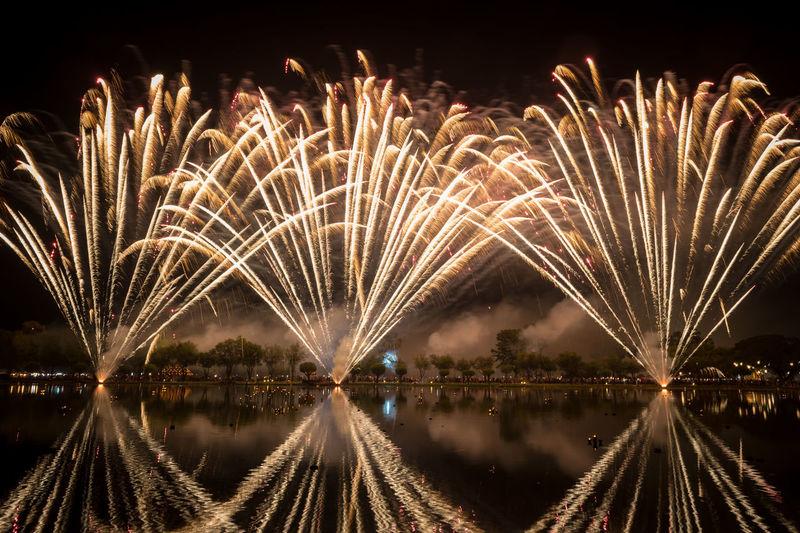 Panoramic view of firework display over lake at night