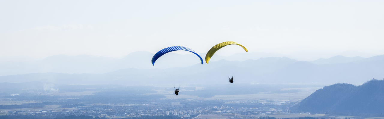 Panoramic view of people paragliding over landscape against sky