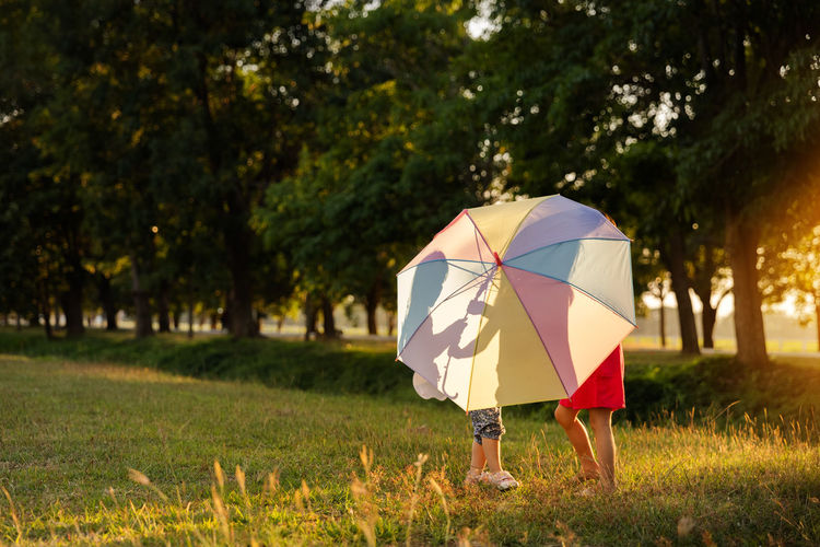 Low section of sibling holding umbrella standing at park
