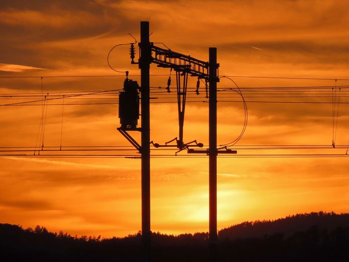 Silhouette electricity pylon against romantic sky at sunset