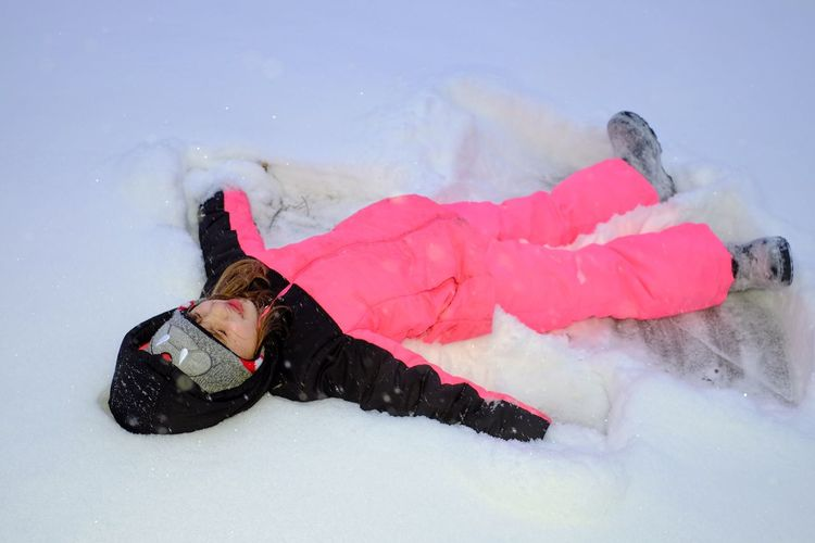 High angle view of girl making snow angel on field