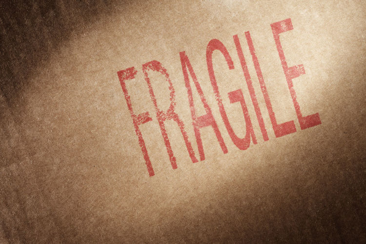 "Closeup of a brown cardboard box with word ""Fragile"" stamped with red ink."