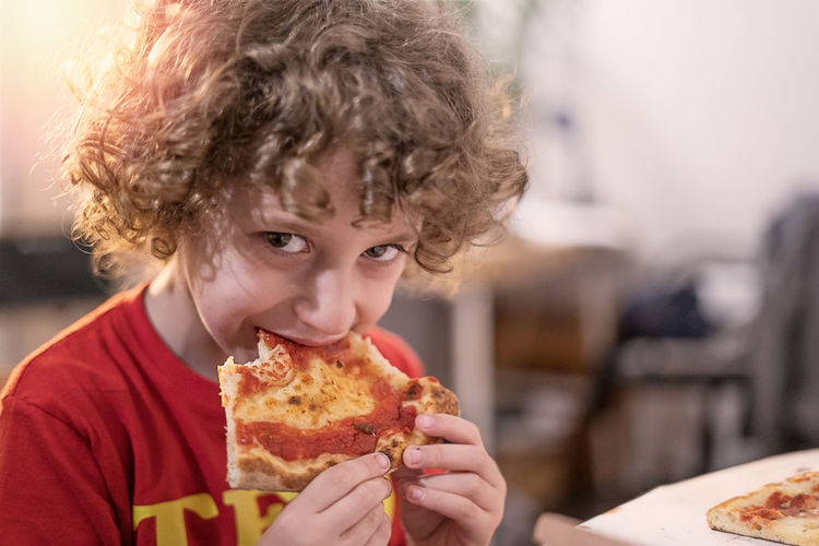 Portrait of boy eating pizza at table