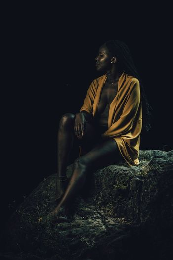 Black woman under a night sky semi with just a sweater sitted on a rock