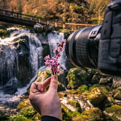 Midsection of man photographing plant against waterfall