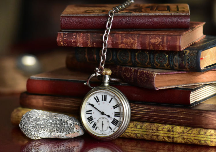 Book Publication Wood - Material Antique Indoors  No People Close-up Table Stack Old Time Still Life Clock Group Of Objects Pocket Watch Focus On Foreground Instrument Of Time History Retro Styled Hardcover Book