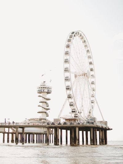 EyeEm Selects Ferris Wheel Amusement Park Ride Amusement Park Sky Travel Destinations Water Built Structure Nature Travel Arts Culture And Entertainment Waterfront Clear Sky No People Copy Space Architecture Sea City Tourism