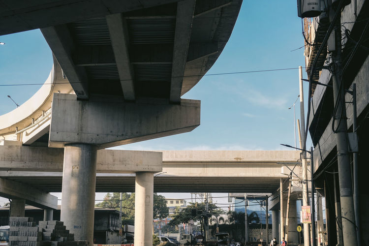 Low angle view of bridge over city street against sky