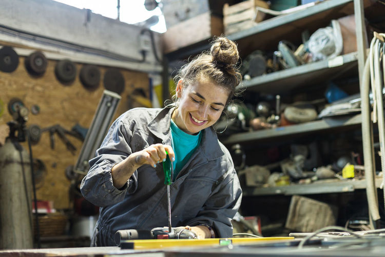 Low Angle View Of Smiling Mid Adult Woman Working On Desk In Workshop