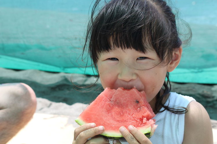 Portrait of girl eating watermelon slice while sitting at beach