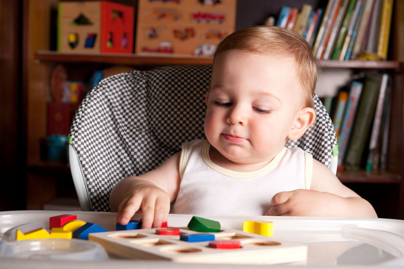 Close-up of baby boy playing with toys on table at home