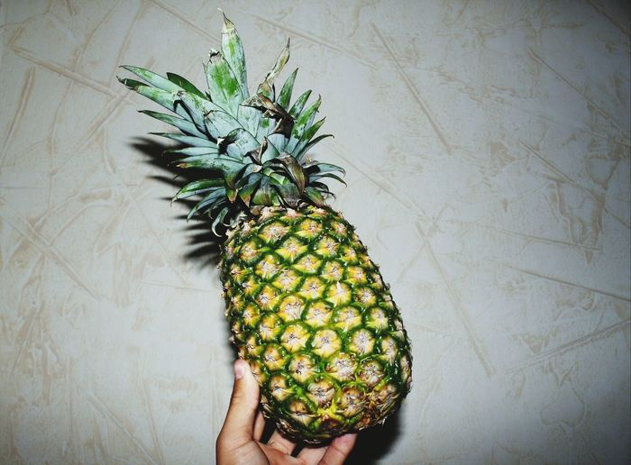 Cropped hand of person holding pineapple against wall