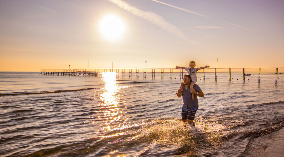 Man Piggybacking Son While Standing At Beach Against Sky During Sunset