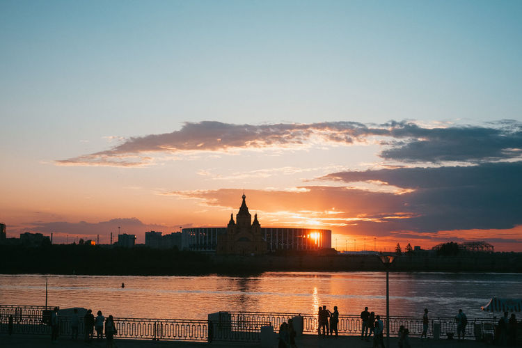 Silhouette of buildings by river during sunset