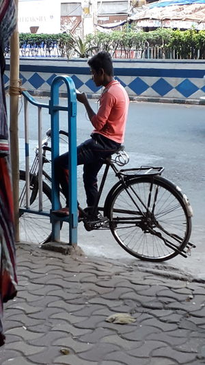 Full length of man sitting on bicycle