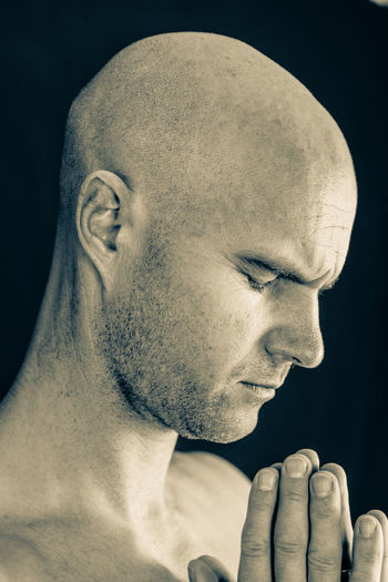 Close-Up Of Shaved Head Man With Hands Clasped Against Black Background