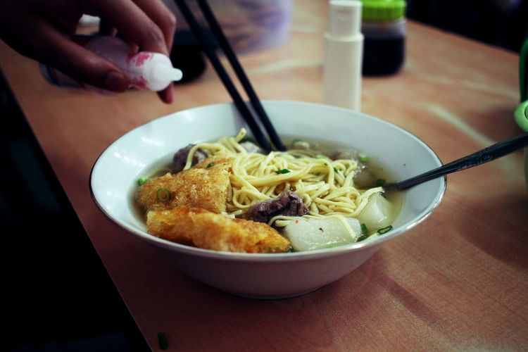 Midsection of person having noodle soup in bowl