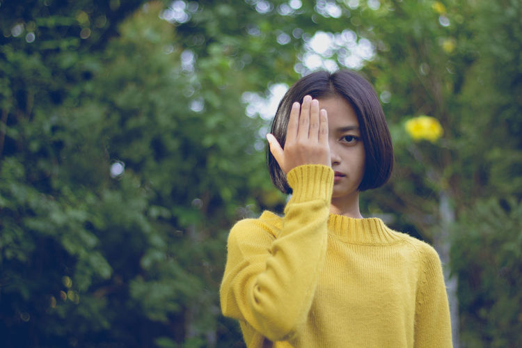 Portrait of teenage girl covering eye with hand against trees