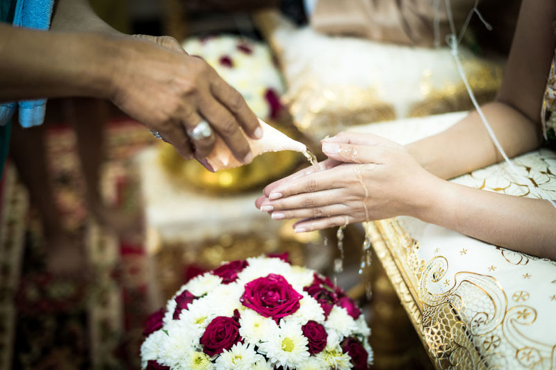 Cropped image of woman pouring water on bride hands during wedding ceremony