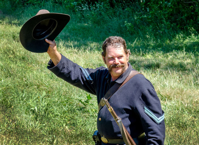 June 2017 Hesston IN USA; a union soldier waves his hat in vicory as he participates in a civil war reenactment event Civil War Hat Uniform Adult Clothing Day Field Front View Grass Holding Land Leisure Activity Males  Mature Adult Mature Men Men Military Nature One Person Real People Reenactment Union Soldier Victory Waist Up Weopons