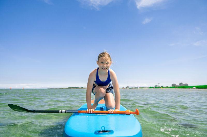 Portrait of happy boy in sea against blue sky