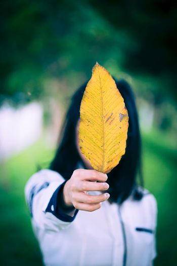 Midsection of woman holding yellow leaf