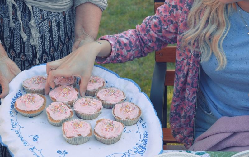 Midsection Of Women Holding Cupcakes In Yard