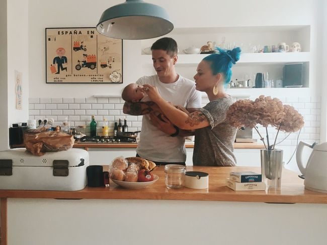 young family Young Adult Lifestyles Casual Clothing Indoors  Leisure Activity Person Food And Drink Young Family Young Parent Mother Fatherhood Moments Father Newborn Togetherness Looking At Camera Confidence  Culture In Front Of Mature Adult