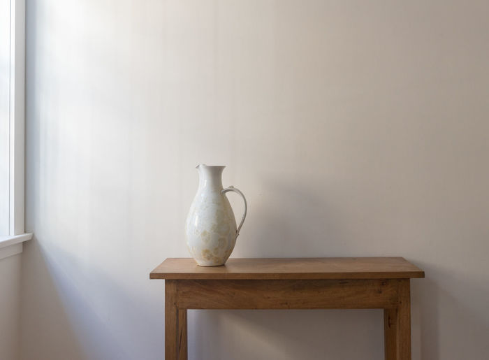 White Pitcher On Table Against Wall At Home