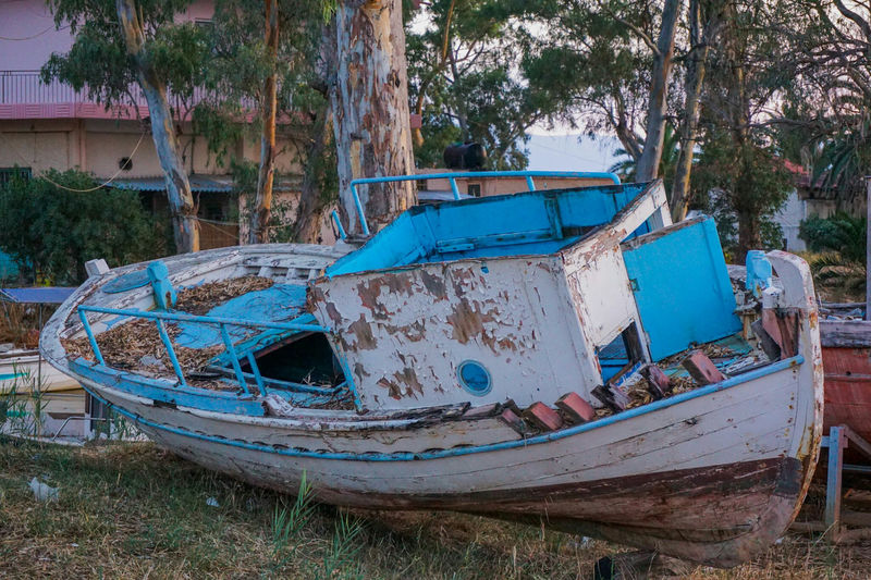 Abandoned obsolete old boat on shore