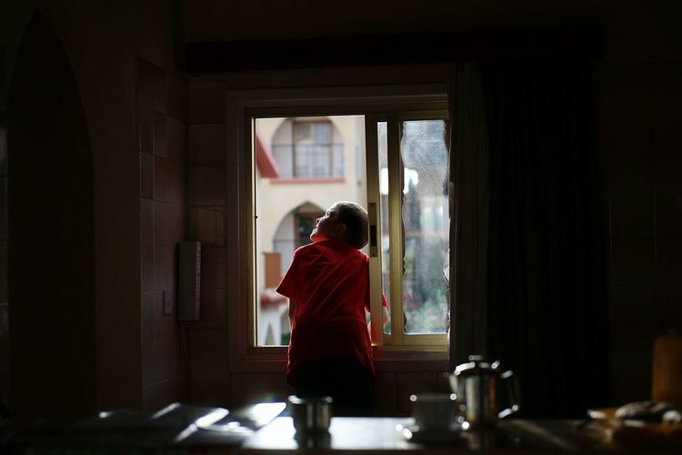 Rear view of boy looking up through window at home