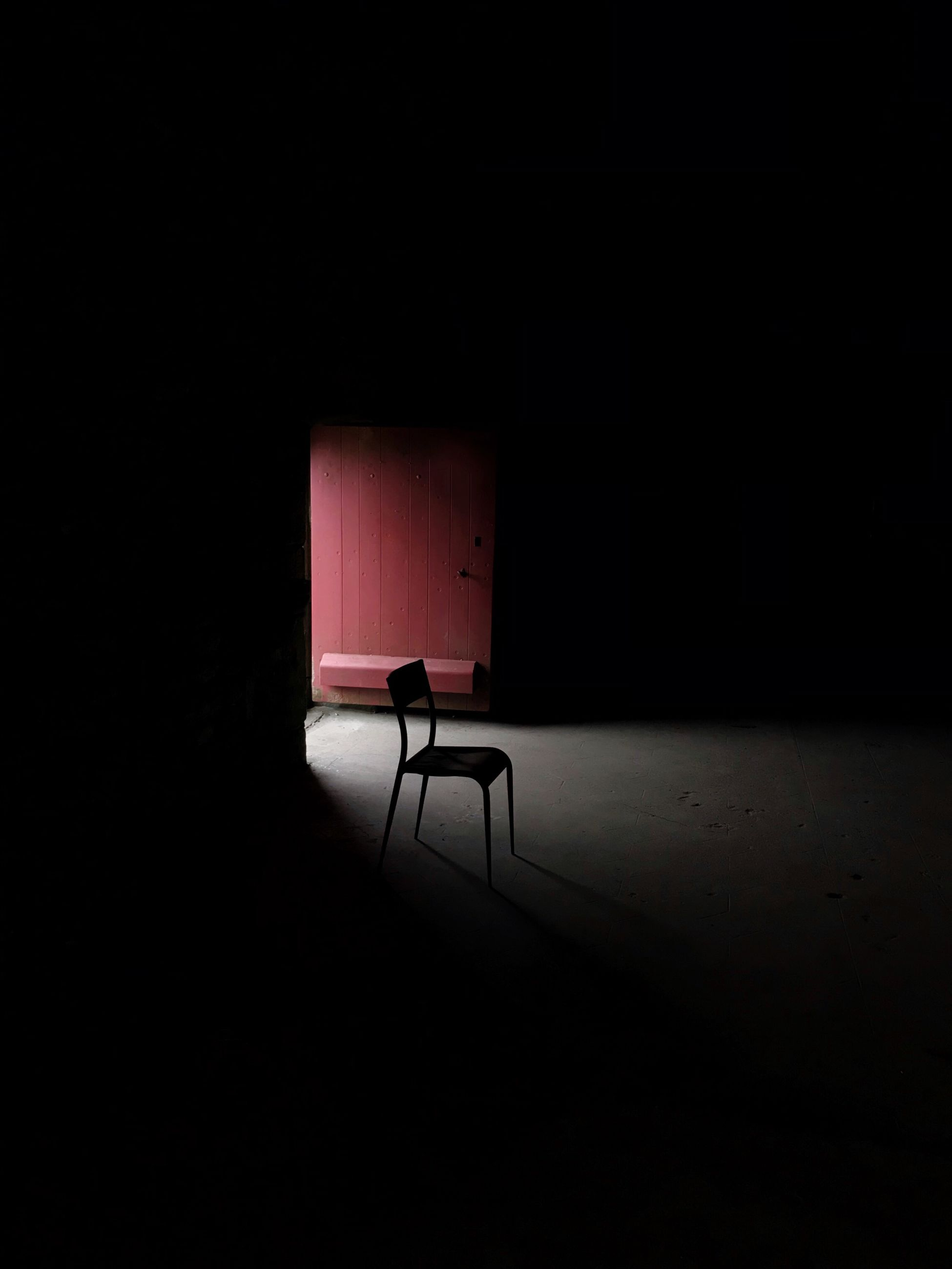 seat, absence, chair, dark, empty, indoors, no people, domestic room, copy space, shadow, spotlight, abandoned, spooky, darkroom, architecture, stage - performance space, solitude, furniture, stage