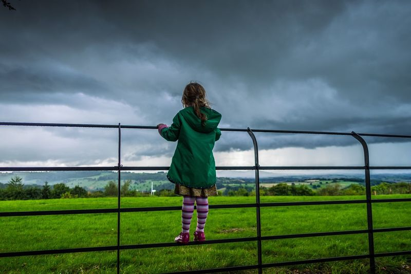 Storm watcher Childhood Full Length Grass Leisure Activity Sky Cloud - Sky Railing Elementary Age Lifestyles Landscape Rear View Cloud Grassy Field Innocence Cloudy Vacations Overcast Casual Clothing Person My Year My View