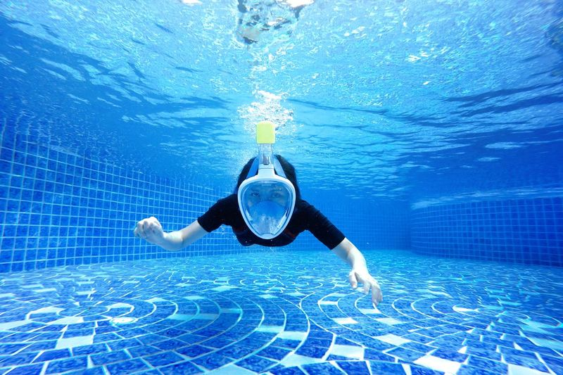 lady put Big diving mask in the pool Blue Eyewear Full Length Healthy Lifestyle Human Arm Leisure Activity Lifestyles Motion Nature One Person Outdoors Pool Real People Sea Shirtless Sport Swimming Swimming Pool Swimwear Underwater Water